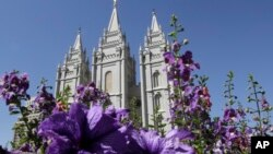 FILE - Flowers bloom in front of the Salt Lake Temple. in Temple Square, in Salt Lake City, Sept. 3, 2014.