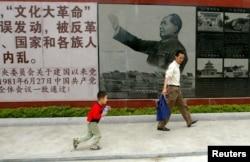 在中国广东省汕头的文革博物馆,参观者在中共前领导人毛泽东在文革期间的照片前面走过 (2006年5月15日)毛泽东所说他一生所做两件大事之一的文革,被中共中央彻底否定。