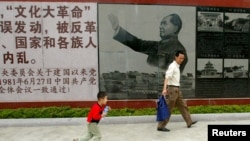 FILE - Visitors walk past a portrait of the late Chinese leader Mao Zedong at the Cultural Revolution Museum in Shantou in China's southern Guangdong province, May 15, 2006.