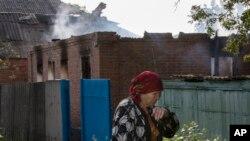 乌克兰东部的一位妇女走过被炮火摧毁的房子