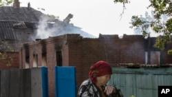 Seorang warga melewati sebuah rumah yang hancur di Semyonovka, sebuah kota kecil dekat Slovyansk, Ukraina (23/5).