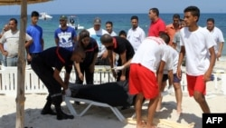Tunisian lifeguards and medics transport a covered body in the resort town of Sousse, a popular tourist destination 140 kilometers (90 miles) south of the Tunisian capital, June 26, 2015. (AFP PHOTO / BECHIR TAIEB)