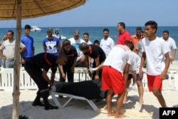 FILE - Tunisian lifeguards and medics transport a covered body in the resort town of Sousse, a popular tourist destination 140 kilometers (90 miles) south of the Tunisian capital, June 26, 2015.