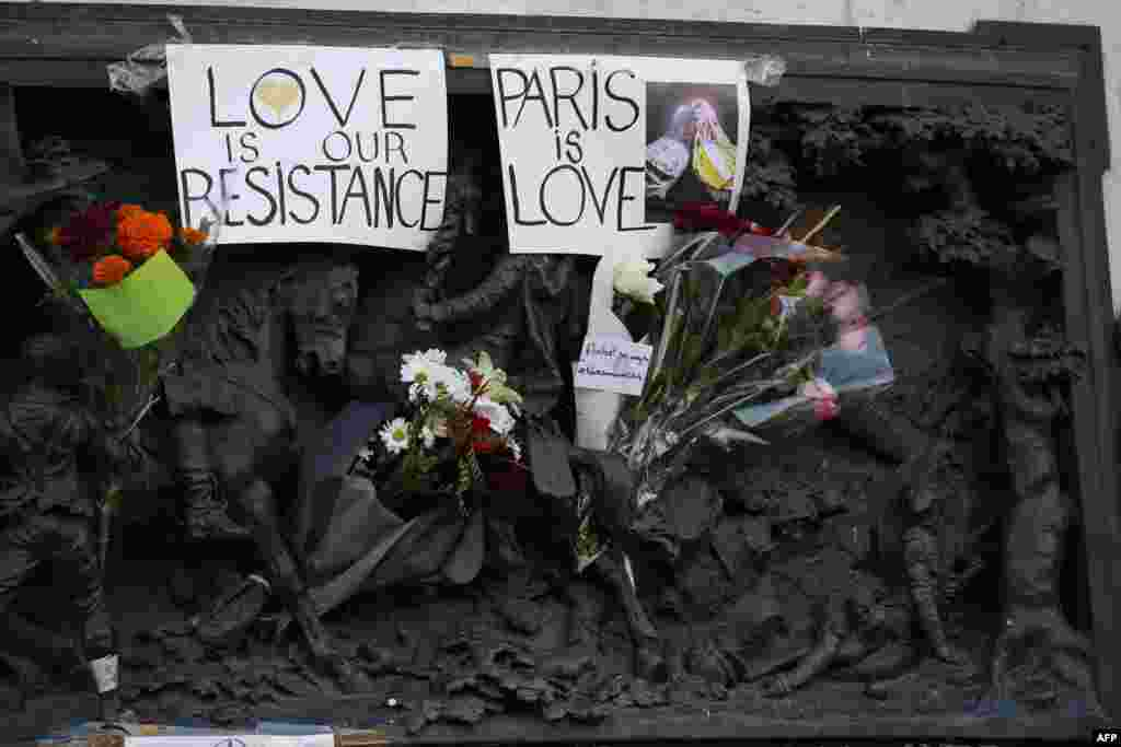 Signs reading 'Love is our resistance' and 'Paris is love' are pictured at the Monument a la Republique, at the Place de la Republique in Paris, on Nov. 15, 2015, two days after a series of deadly attacks.