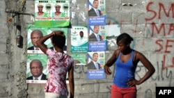A wall is plastered with campaign posters of political candidates in the commune of Delmas, Port-au-Prince, on Aug. 5, 2015.