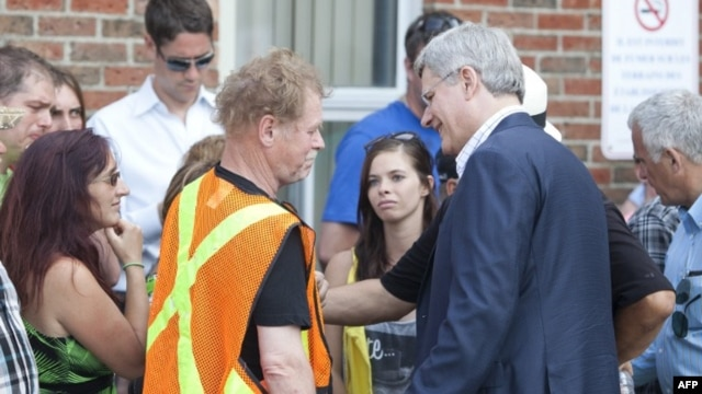 Canadian Prime Minister Stephen Harper greets families following a press conference at Lac-Mégantic high school on July 7, 2013 in Lac-Megantic, Quebec, Canada, one day after a train derailment and subsequent explosion and fire.