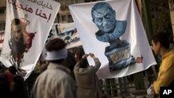 무바라크 대통령의 포스터를 들고 시위를 하는 이집트인들