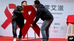 Men move a red ribbon display at an event to promote awareness of HIV testing ahead of the December 1 World AIDS Day, in Beijing, China, Nov. 27, 2014.