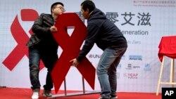 Dua pria memindahkan pita merah dalam acara untuk mendorong kesadaran akan uji HIV di Beijing, China (27/11). (AP/Ng Han Guan)