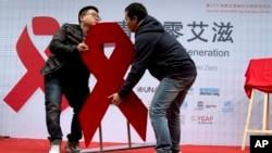 ຊາຍໜຸ່ມສອງຄົນ ເຄື່ອນຍ້າຍ ໂບແດງ ຕັ້ງໂຊ ທີ່ງານສົ່ງເສີມ ຈິດສຳນຶກ ໃນການກວດຫາເຊື້ອ HIV ກອນໜ້າວັນທີ 1 ທັນວາ ຊຶ່ງເປັນມື້ World AIDS Day ໃນນະຄອນຫລວງປັກກິ່ງ ປະເທດຈີນ, ວັນທີ 27 ພະຈິກ 2014.