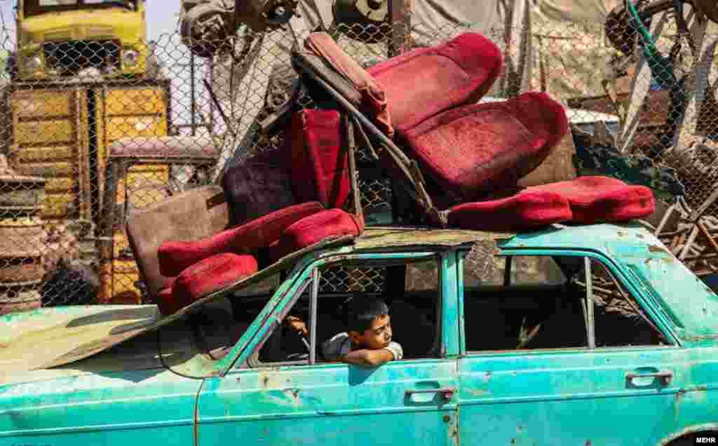 پسر بچه در گورستان خودروهای فرسوده در تهران بازی میکند.