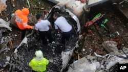 FILE: Rescuers stand amid the wreckage of a private chartered plane that crashed.