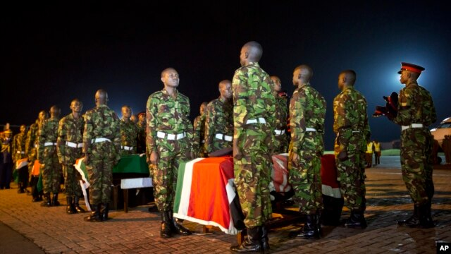Military pallbearers stand to attention next to the coffins of four Kenyan soldiers who were killed in Somalia, at a ceremony to receive their bodies which were airlifted to Wilson Airport in Nairobi, Kenya, Jan. 18, 2016.