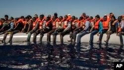 지난 19일 리비아 북쪽 지중해 해상에서 고무보트에 탄 난민과 이민자들이 구조를 기다리고 있다. 이들은 에리트레아와 말리, 방글라데시 등 여러 나라 출신이었다.
