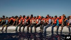 In this Tuesday July 19, 2016 photo, refugees and migrants from Eritrea, Mali, Bangladesh and other countries wait on board a dinghy to be rescued in the Mediterranean Sea, 27 kilometers (17 miles) north of Sabratha, Libya