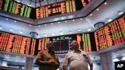 Dua orang pria tengah mengamati papan perdagangan di sebuah galeri bursa saham swasta di Kuala Lumpur, Malaysia (25/8).