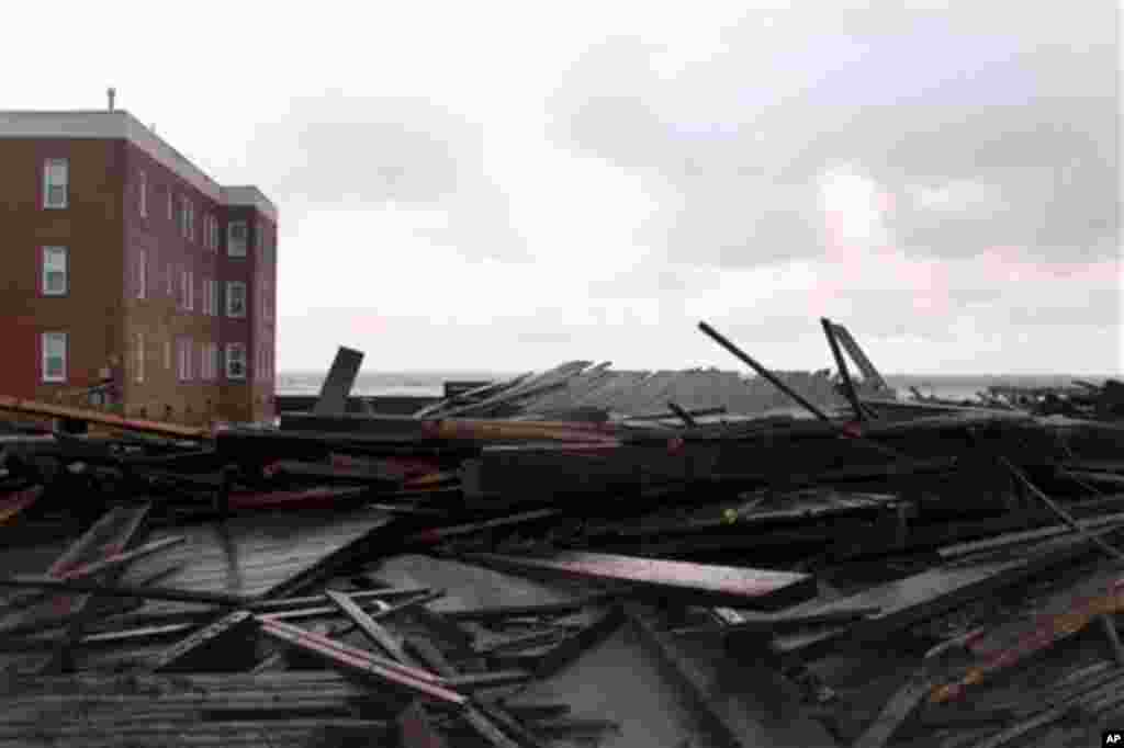 Large chunks of the boardwalk are piled near an apartment building on the ocean in Atlantic City, New Jersey, October 30, 2012.