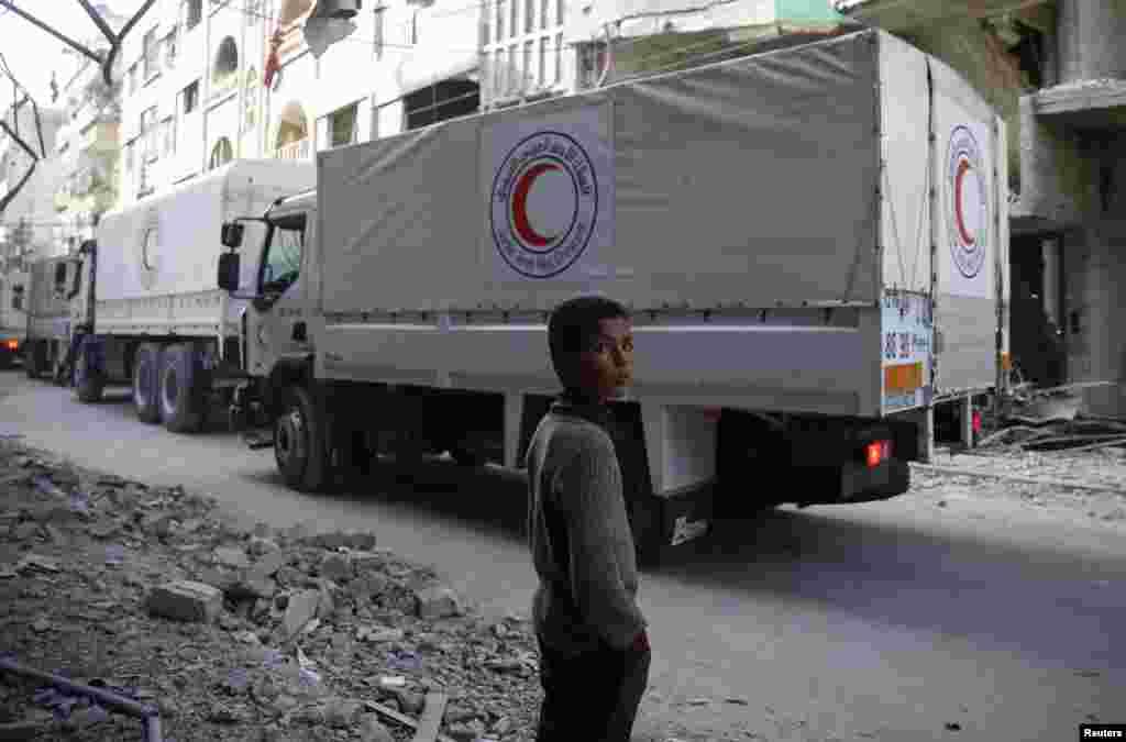 ក្មេងប្រុសម្នាក់ឈរនៅជិតរថយន្តជំនួយស៊ីរីអារ៉ាប់ដែកបើកកាត់ទីក្រុង Doumaដែលកាន់កាប់ដោយក្រុមឧទ្ទាមនៅរដ្ឋធានី Douma។