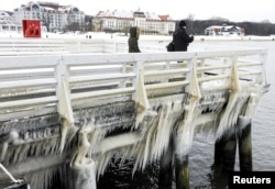People walk along an ice-covered pier in Sopot, Poland, Jan. 9, 2017.