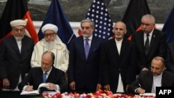 Afghan National Security Adviser Hanif Atmar (R) and US Ambassador to Afghanistan James Cunningham (L) sign security agreement in Kabul, Sept. 30, 2014. (AFP PHOTO/SHAH Marai)