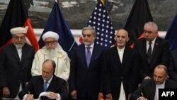 Avganistanski savetnik za nacionalnu bezbednost Hanif Atmar i američki ambasador u Avganistanu Džejms Kaningem potpisuju sporazum o bezbednosti u prisustvu najviših avganistanskih zvaničnika
