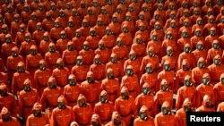 2021 年 9 月 9 日在平壤金日成广场举行的朝鲜国庆73周年的检阅仪式上穿着橙色防护服的人员在行进。(路透社)