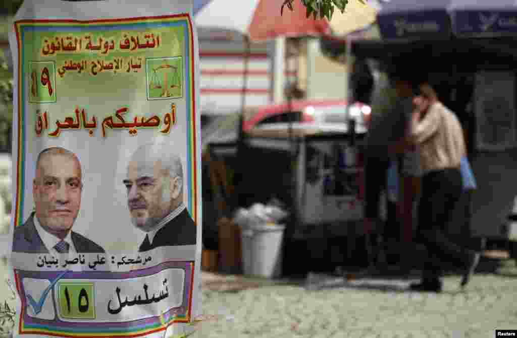 "An Iraqi walks past a provincial elections campaign poster in Baghdad, April 18, 2013. Iraq will hold its provincial elections on Saturday. The poster reads, ""take care of Iraq."""