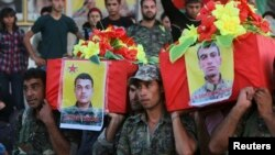 FILE - Members of the Kurdish People's Protection Units (YPG) carry coffins of their fellow fighters, who were killed during clashes with Islamic State fighters on the Iraqi-Syrian border, during their funeral in Ras al-Ain city, in Syria's Hasakah provin