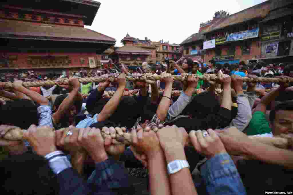 Devotees pull the rope tied to the chariot of God Bhairab through the city center of Bhaktapur near Kathmandu, Nepal, during the Bisket festival.