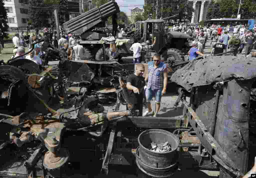 People inspect damaged heavy hardware from the Ukrainian army during an exhibition on central square in Donetsk, eastern Ukraine, Aug. 24, 2014.