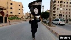 一名伊斯兰国武装分子在伊拉克的一个城镇挥舞伊斯兰国的旗子。(资料照片)