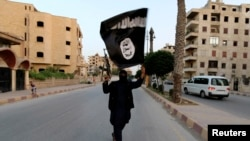 FILE - A man waves an Islamic State flag on the streets of Raqqa, Syria, in 2014. German authorities have arrested a Syrian doctoral student in Darmstadt; he's suspected of promoting IS and its symbols on social media.