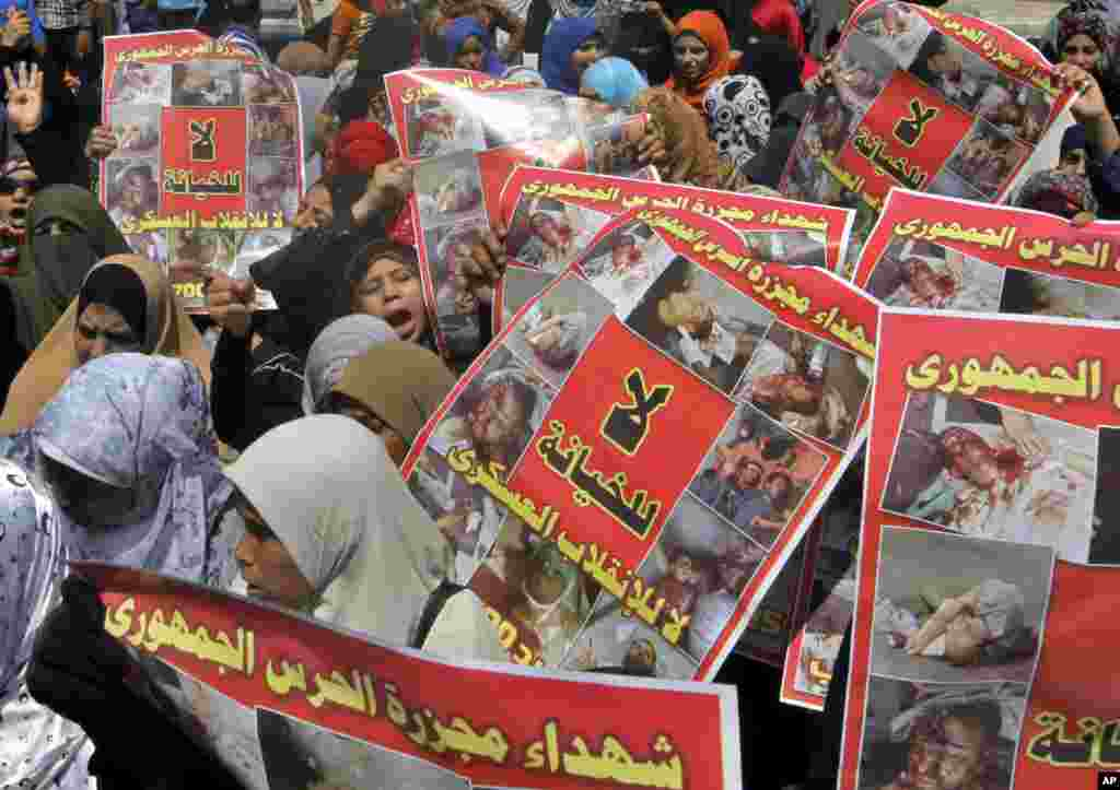 Supporters of Egypt's ousted President Mohamed Morsi hold posters showing victims of a military crackdown on their protest camp during a march in Cairo, August 23, 2013.