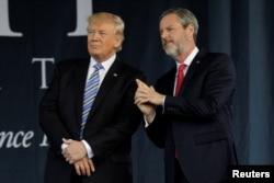 President Donald Trump, left, stands with Liberty University President Jerry Falwell Jr. after delivering the keynote address at commencement in Lynchburg, Virginia, May 13, 2017.