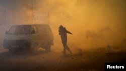 بیروت میں حکومت کی تبدیلی کے لیے مظاہرے جاری ہیں۔ مظاہرے میں شامل ایک شخص اشک آور گیس سے بچنے کے لیے بھاگ رہا ہے۔ 18 جنوری 2019