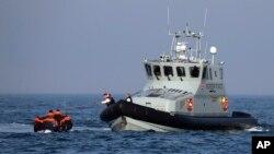 Sebuah Kapal Penjaga Perbatasan Inggris membantu sekelompok migran yang terapung-apung di atas perahu karet mereka di perairan Selat Inggris.