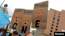"Opposition supporters hold placards during a rally to demand a referendum to remove President Nicolas Maduro in Caracas, Venezuela, May 14, 2016. From left, the placards read ""Deaf,"" ""Blind"" and ""Dumb."" ""CNE"" on the placards refers to the National Electoral Council."