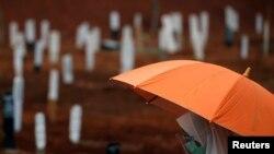 Seorang perempuan mengenakan masker dan pelindung wajah berdoa saat pemakaman seorang kerabat di pemakaman khusus jenazah pasien Covid-19 di TPU Pondok Rangon, Jakarta, 24 September 2020. (Foto: Reuters)