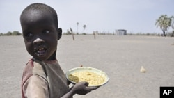 A young boy walks away with his food from a government sponsored feeding center in central Turkana, Kenya, August 30, 2011