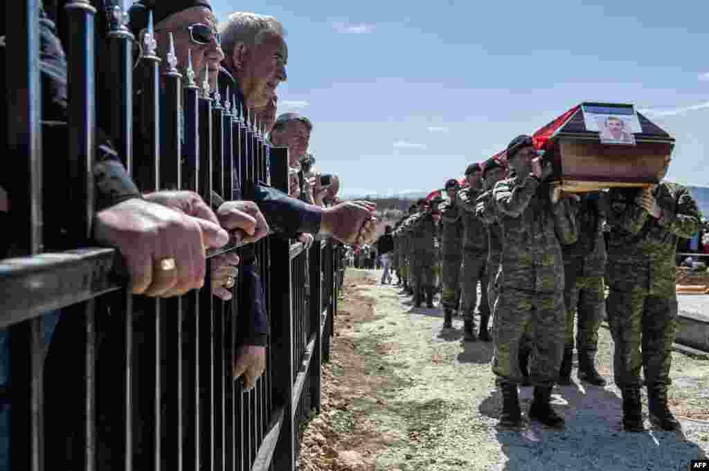 Members of the Kosovo Security Force (KSF) carry the coffins containing the remains of 21 Kosovo Albanians allegedly killed by Serbian security forces during the 1998-1999 Kosovo war, during a funeral ceremony in the village of Qikatove. The remains were identified after being dug out from a mass grave in Serbia.