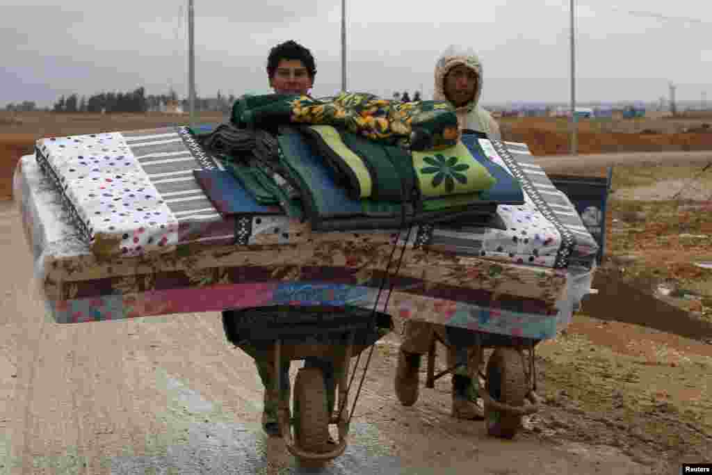 Syrian refugees transport their belongings after heavy rain at the Al Zaatari refugee camp in the Jordanian city of Mafraq, Dec. 12, 2013.