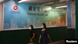 行人走过香港政府在街头张贴的港版国安法宣传标语。(2020年6月29日)