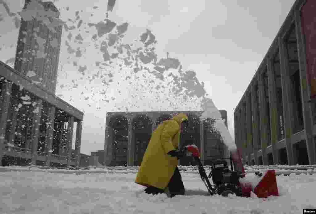 A worker uses a snow blower to clear snow off the steps at Lincoln Center, the site of New York Fashion Week, in the Manhattan borough of New York, Feb. 13, 2014.
