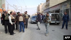 Armed tribesmen and Iraqi police stand guard in a street as clashes rage on in the Iraqi city of Ramadi, West of Baghdad, on January 2, 2014.
