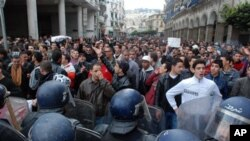 ຊາວອາລຈີເຣຍໂຮມຊຸມນຸມປະທ້ວງ ຢູ່ຈະຕຸລັດ May 1st ຫລືວັນທີ 1 ພຶດສະພາ ກໍຄືວັນກໍາມະກອນສາກົນ, ຮຽກຮ້ອງໃຫ້ປະທານາທິບໍດີ Abdelaziz Bouteflika ລາອອກ, ວັນທີ 13 ກຸມພາ 2011.