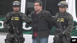 Joaquin Perez, a suspected Revolutionary Armed Forces of Colombia, or FARC rebel is escorted by policemen after his arrival at Bogota police anti-drugs hangar and airport base April 25, 2011.