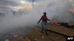 Une femme passe devant une cabane incendiée près d'un chemin de fer par des manifestants dans le bidonville de Kibera à Nairobi le 12 août 2017.