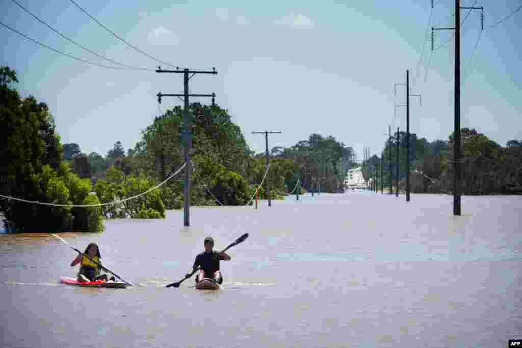 Kayakers paddle on the flooded Logan River, caused by Cyclone Debbie, as it flows over the Mt. Lindesay Highway in Waterford West near Brisbane, Australia, April 1, 2017.