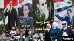 Ahead of Tuesday's election, women walk past election posters of Syria's President Bashar al-Assad along a street in Damascus, Syria, June 2, 2014.