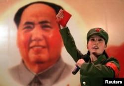 """打扮成红卫兵的少女手持《毛主席语录》,在北京一家名为""""红色经典""""的餐厅中的毛主席像前表演(2006年4月7日)"""